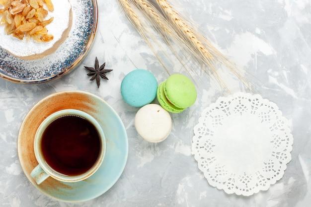 Vista de cima redondo pequeno bolo de açúcar em pó com chá de passas e macarons na superfície branca