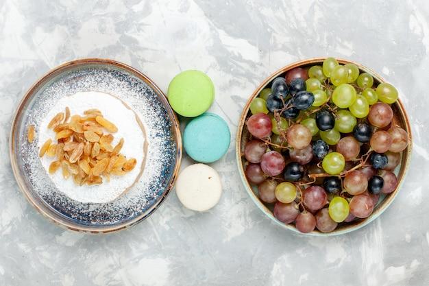 Vista de cima redondo pequeno bolo de açúcar em pó com passas, macarons franceses e uvas na mesa branca