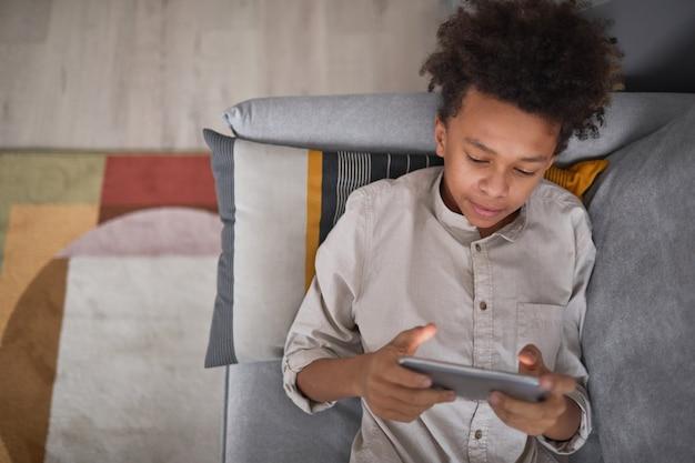 Vista de cima, retrato médio de um menino adolescente relaxando no sofá em casa jogando videogame no smartphone, copie o espaço