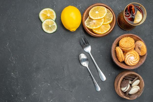 Vista de cima rodelas de limão fresco com biscoitos na superfície escura