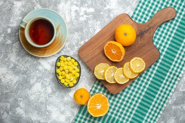 Vista de cima rodelas de limão fresco com doces e xícara de chá na mesa de luz