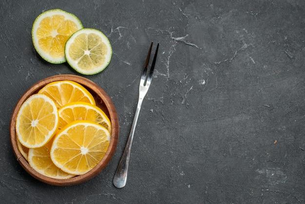 Vista de cima rodelas de limão fresco em superfície escura