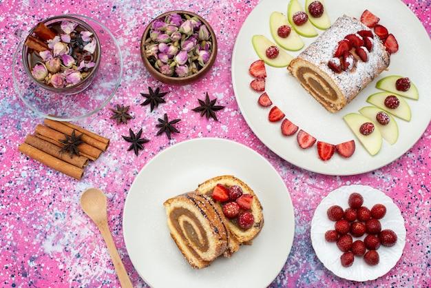 Vista de cima rolar fatias de bolo com frutas diferentes dentro de prato branco com canela também no fundo colorido bolo biscoito cor doce
