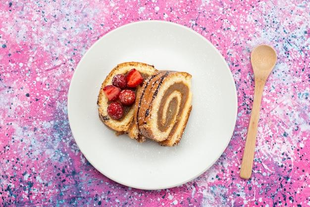 Vista de cima rolar fatias de bolo dentro de um prato branco com fatias de morango na mesa roxa bolo biscoito açúcar doce foto