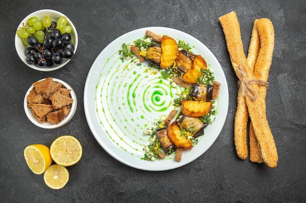 Vista de cima rolinhos de berinjela cozida com uvas, pão e rodelas de limão em fundo escuro prato jantar refeição frutas cozinhar