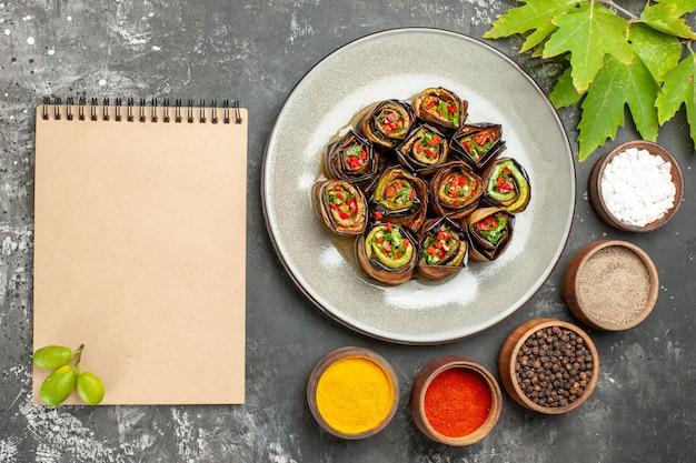 Vista de cima rolinhos de berinjela recheada em um prato oval branco, especiarias diferentes em pequenas tigelas um caderno em fundo cinza