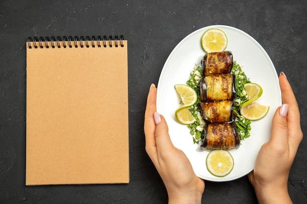 Vista de cima, rolinhos de berinjela salgados prato cozido com rodelas de limão na superfície escura e óleo para cozinhar prato de refeição