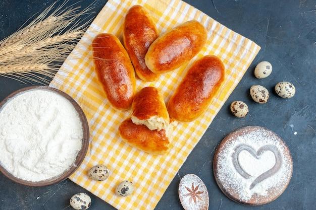 Vista de cima rolos de café da manhã em toalha de cozinha tigela de farinha ovos de codorna coração impresso em açúcar de confeiteiro na mesa