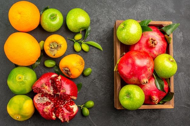 Vista de cima romãs frescas com maçãs e outras frutas na superfície escura de frutas maduras