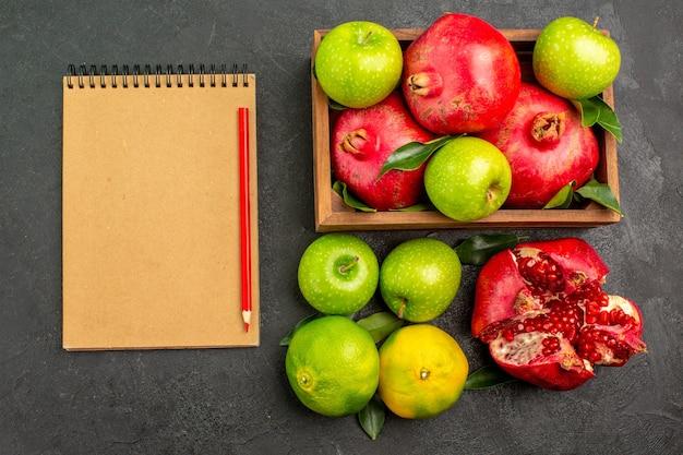 Vista de cima romãs frescas com maçãs e tangerinas em frutas maduras de superfície escura