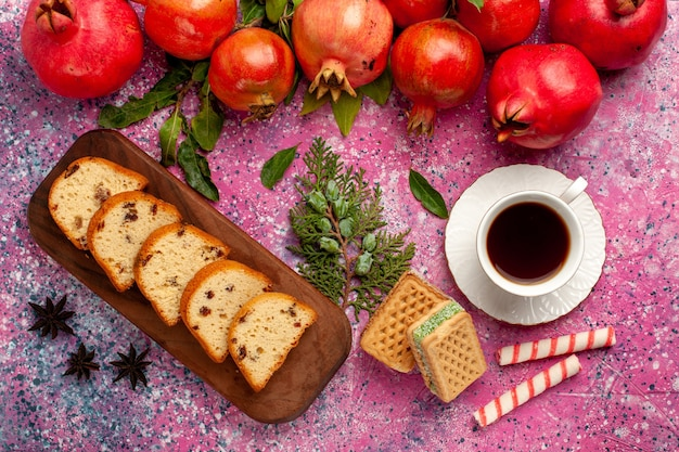 Vista de cima romãs vermelhas frescas com bolo fatiado, chá e waffles na superfície rosa