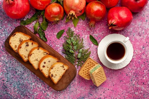 Vista de cima romãs vermelhas frescas com bolo fatiado e waffles na superfície rosa