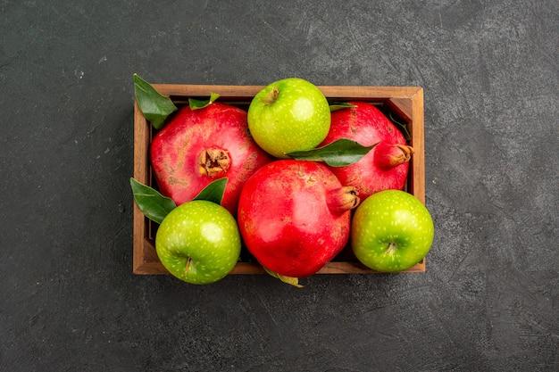 Vista de cima romãs vermelhas frescas com maçãs verdes em uma superfície escura de cor de fruta madura