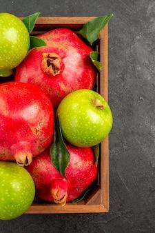 Vista de cima romãs vermelhas frescas com maçãs verdes na superfície escura com frutas maduras