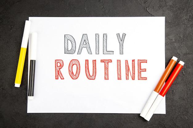 Vista de cima rotina diária escrita em branco com lápis na superfície escura note bloco de notas fotográfico colorido caderno