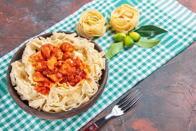 Vista de cima saborosa massa cozida com frango e molho em prato de refeição de massa no chão escuro