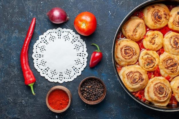 Vista de cima saborosa refeição de massa com carne dentro da panela junto com vegetais frescos, como cebola, tomate na mesa cinza escuro.