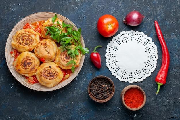 Vista de cima saborosa refeição de massa com carne dentro do prato junto com vegetais frescos, como cebolas, tomates na mesa cinza-escuro.
