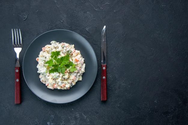 Vista de cima saborosa salada de frango com diferentes vegetais cozidos e maionese dentro do prato na superfície escura cores dos alimentos