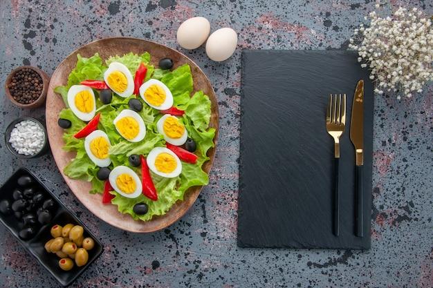 Vista de cima saborosa salada de ovo com salada verde e azeitonas em fundo claro