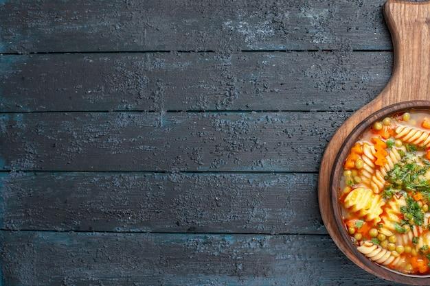 Vista de cima saborosa sopa de macarrão com macarrão espiral italiano com verduras em um prato azul escuro de cozinha de mesa