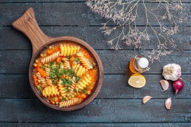 Vista de cima saborosa sopa de macarrão com macarrão espiral italiano com verduras na mesa azul-escuro cor da sopa prato italiano de massa
