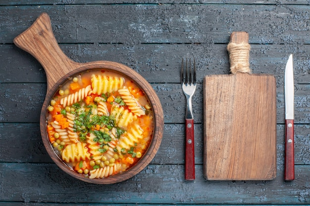 Vista de cima saborosa sopa de massa de macarrão espiral italiano com verduras na mesa azul escuro prato de sopa cor culinária italiana