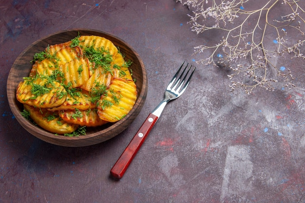 Vista de cima saborosas batatas cozidas com verduras dentro de um prato marrom em um prato de refeição de superfície escura cozinhando batatas cips para o jantar