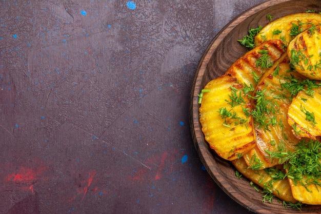 Vista de cima saborosas batatas cozidas com verduras dentro do prato na superfície escura cozinhando batatas fritas jantar