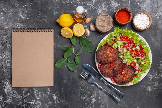 Vista de cima saborosas costeletas de carne com salada de vegetais no fundo cinza foto prato de refeição