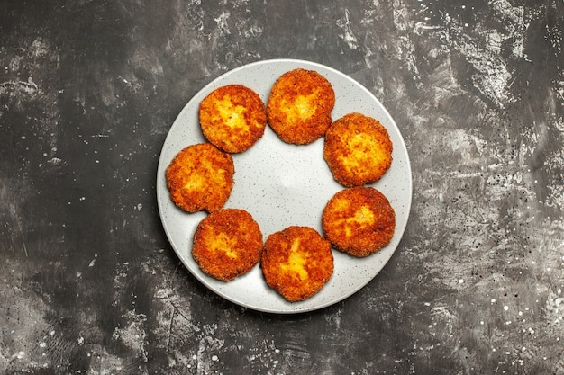 Vista de cima saborosas costeletas fritas dentro do prato em um prato de rissole de carne com superfície escura
