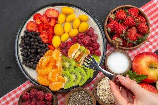 Vista de cima saborosas frutas fatiadas com frutas frescas e frutas em fundo escuro