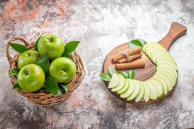 Vista de cima saborosas maçãs verdes com frutas fatiadas no fundo claro