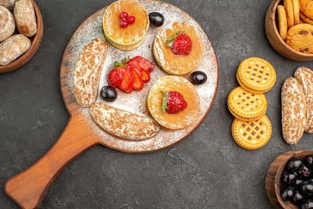 Vista de cima saborosas panquecas com bolos doces e frutas em uma superfície escura e sobremesa
