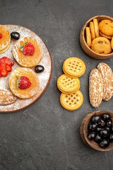 Vista de cima saborosas panquecas com bolos doces e frutas em uma superfície escura, sobremesa de bolos de açúcar