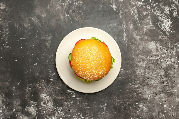 Vista de cima saboroso hambúrguer de frango com legumes no pão de fast-food sanduíche de superfície escura