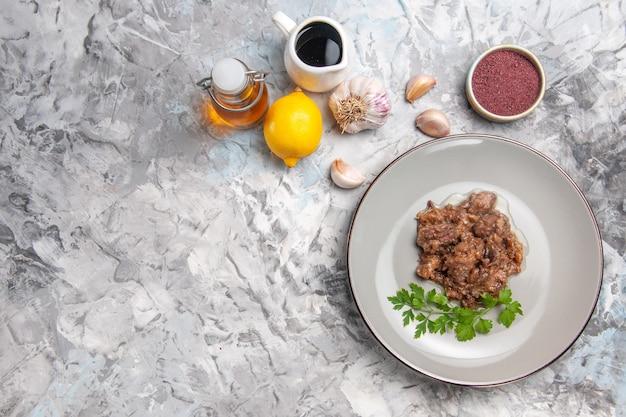Vista de cima saboroso prato de carne com molho e verduras na mesa de jantar branca refeição prato de carne
