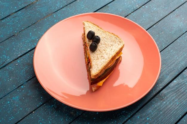 Vista de cima saboroso sanduíche com presunto verde-oliva e tomate dentro da placa rosa no fundo de madeira azul