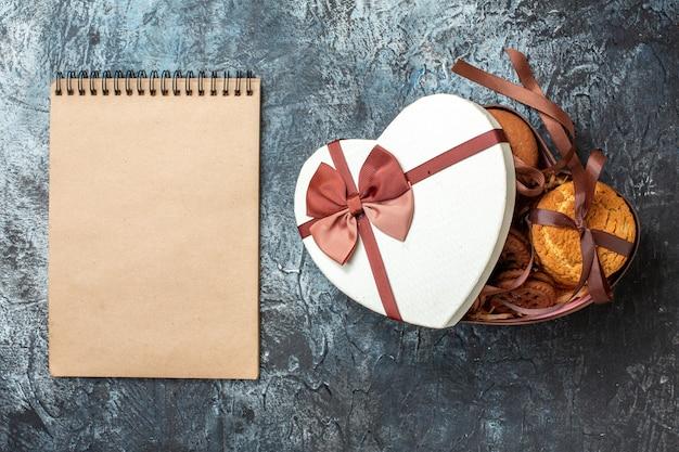 Vista de cima saborosos biscoitos amarrados com corda em uma caixa em forma de coração com bloco de notas de capa na mesa cinza