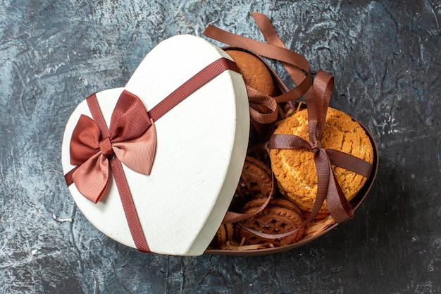 Vista de cima saborosos biscoitos amarrados com corda em uma caixa em forma de coração com capa em fundo escuro