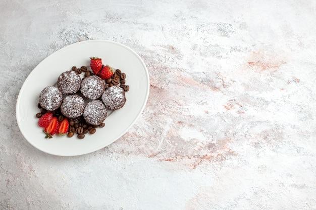 Vista de cima saborosos bolos de chocolate com morangos e gotas de chocolate em uma superfície branca.