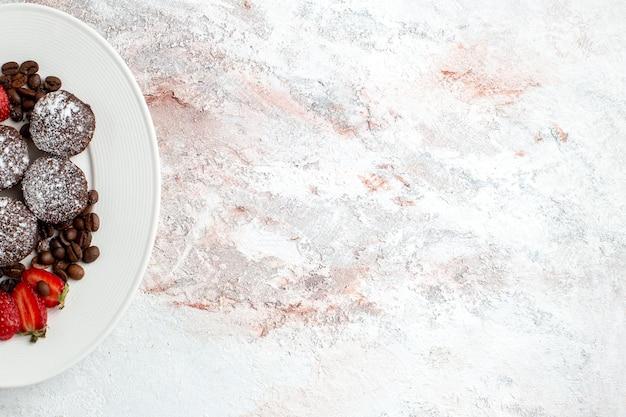Vista de cima saborosos bolos de chocolate com morangos e gotas de chocolate na superfície branca