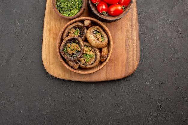 Vista de cima saborosos cogumelos cozidos com tomates no chão escuro