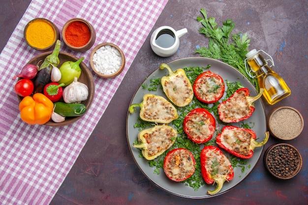 Vista de cima saborosos pimentões deliciosos pratos cozidos com carne e verduras na superfície escura prato de jantar pimenta picante