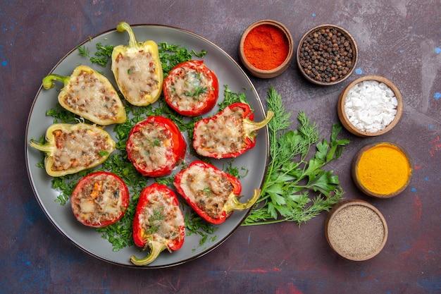 Vista de cima saborosos pimentões deliciosos pratos cozidos com verduras de carne e temperos na superfície escura.