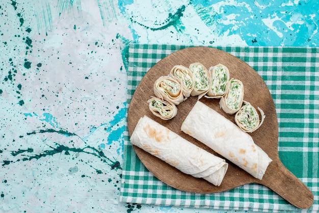 Vista de cima saborosos rolos de vegetais inteiros e fatiados com verduras no fundo azul do rolo de refeição alimentar
