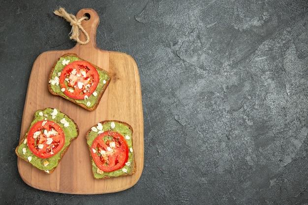 Vista de cima saborosos sanduíches de abacate com fatias de tomate vermelho no fundo cinza sanduíche de hambúrguer com pão e pão.