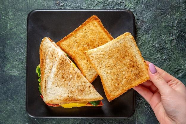 Vista de cima saborosos sanduíches de presunto com torradas dentro do prato em superfície escura