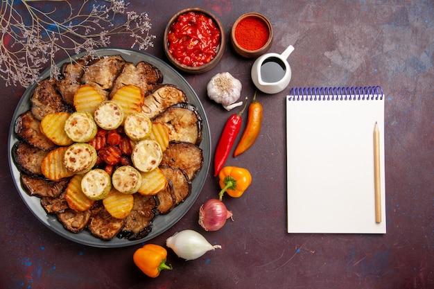 Vista de cima saborosos vegetais assados, batatas e berinjelas em uma refeição em fundo escuro, cozinhando, assar vegetais
