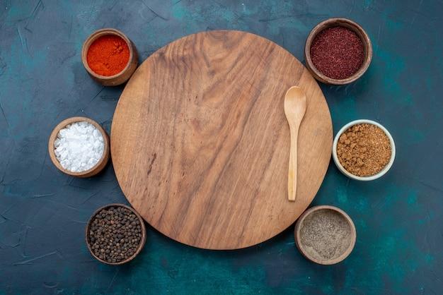 Vista de cima sal e pimenta com outros temperos na mesa azul-escura com ingredientes para pimenta